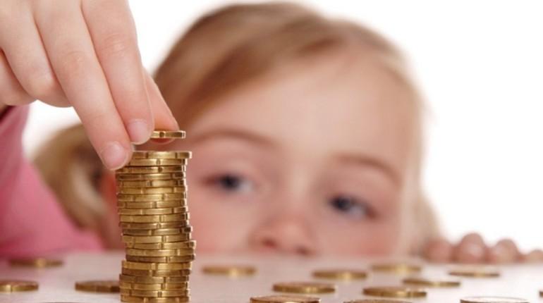 девочка смотрит на монетки, дети учатся обращаться с деньгами, воспитание ребенка