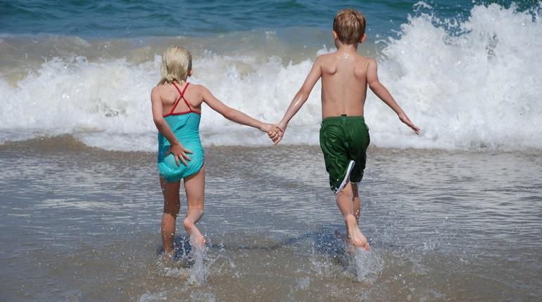 дети на море, брат и сестра за руку идут в море,