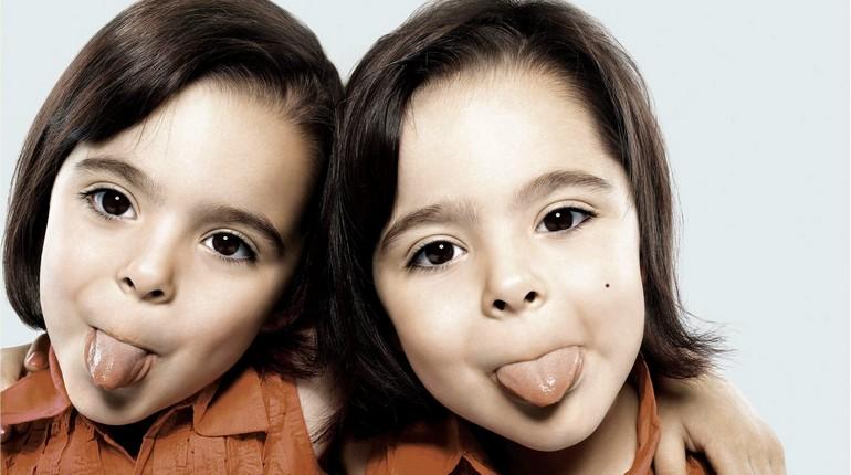 два одинаковых ребенка показывают языки, близняшки, двойняшки девочки