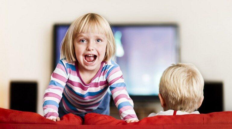 девочка прыгает на диване, дети на диване, девочка смотрит в камеру