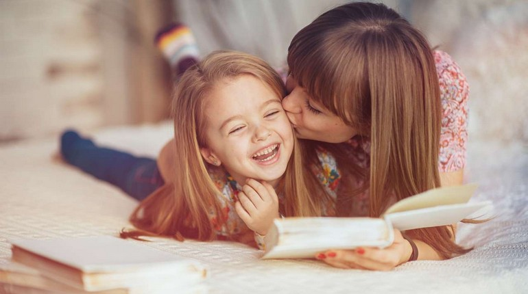 мама целует девочку, дочка счастлива рядом с мамой