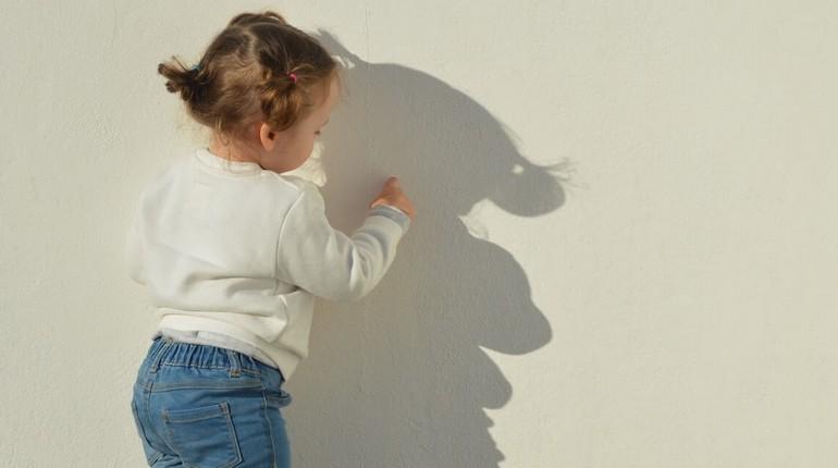 девочка стоит возле стены, девочка и ее тень