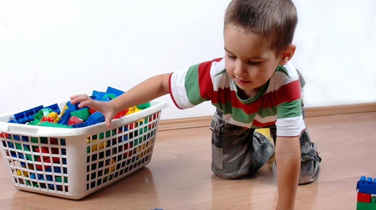 ребенок складывает свои игрушки, мальчмк убирает игрушки в корзинку