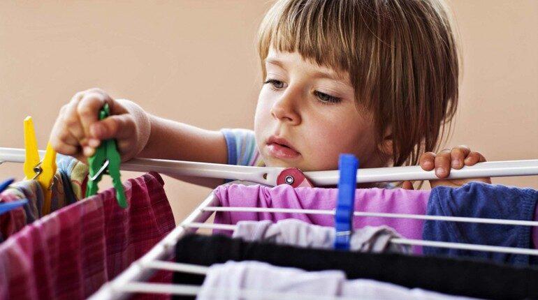 девочка развешивает белье после стирки, дети помогают родителям
