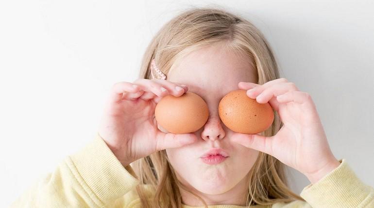 девочка приложила к глазам яйца, девочка балуется