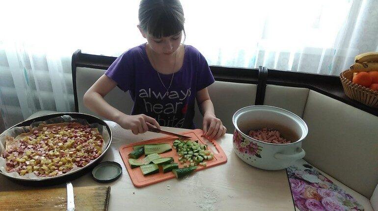 девочка на кухне, ребенок делает сплат. девочка нарезает овощи