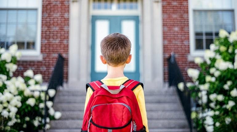 ребенок стоит лицом к школе, мальчик со школьным рюкзаком, парень идет в школу
