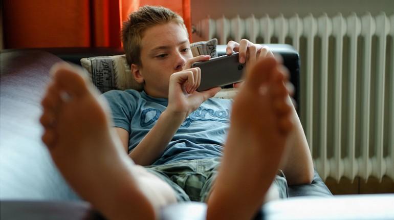 мальчик лежит и смотрит в телефон, подросток смотрит в смартфон