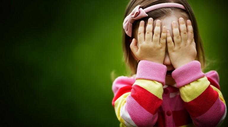 девочка закрыла лицо руками,малышка стесняется