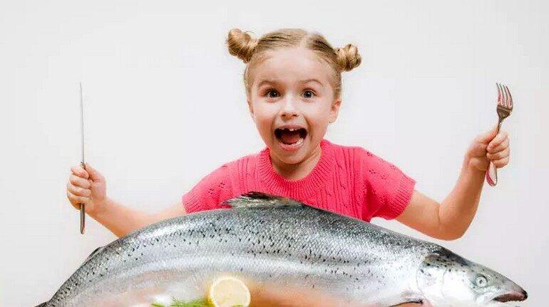 девочка и рыба на столе, ребенок радуется и держит огромную рыбину
