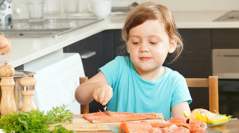 девочка на кухне режет рыбу, лосось на столе и юная хозяйка