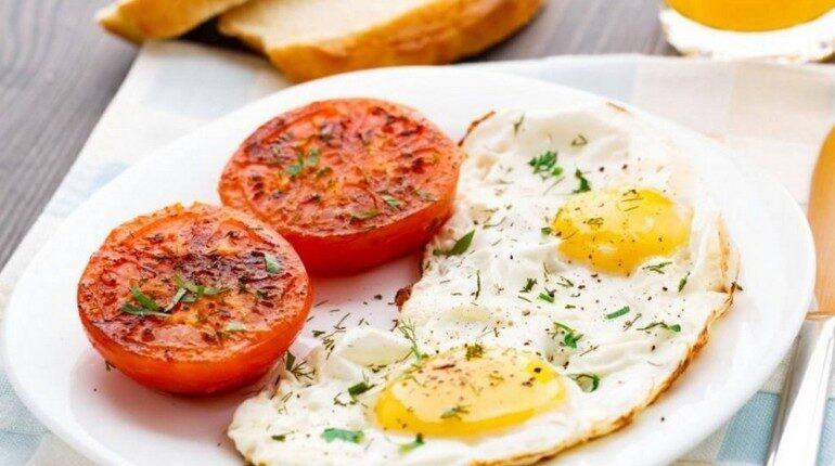 завтрак для школьника, яичница и помидоры в тарелке