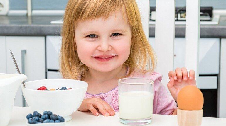 девочка кушает за столом, ребенок завтракает, стакан молока и пиалка на столе за завтраком у девочки