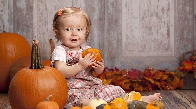 маленькая девочка сидит возле большой тыквы и держит в руке маленькую, малышка позирует с тыквами