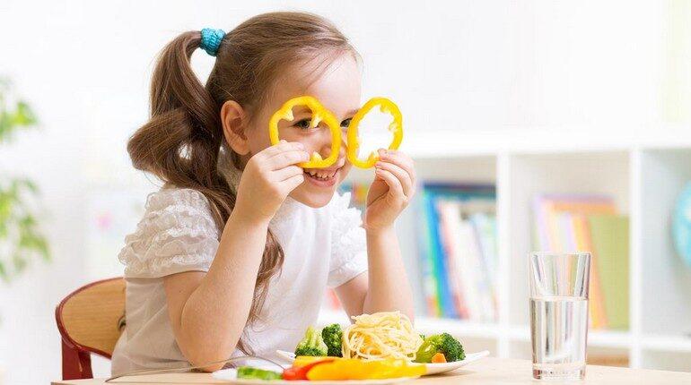 девочка балуется за столом, кружки от болгарского перца девочка приложила к своим глазам