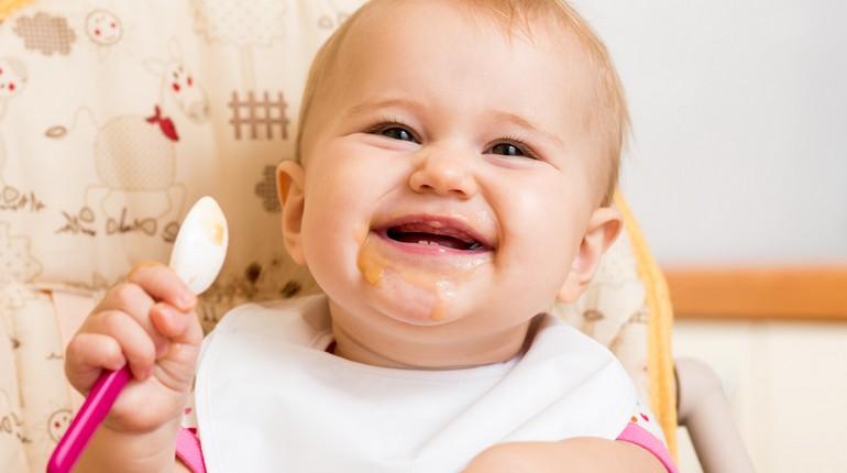 малыш улыбается, младенец до года в слюнявчике, ребенок кушает с ложки