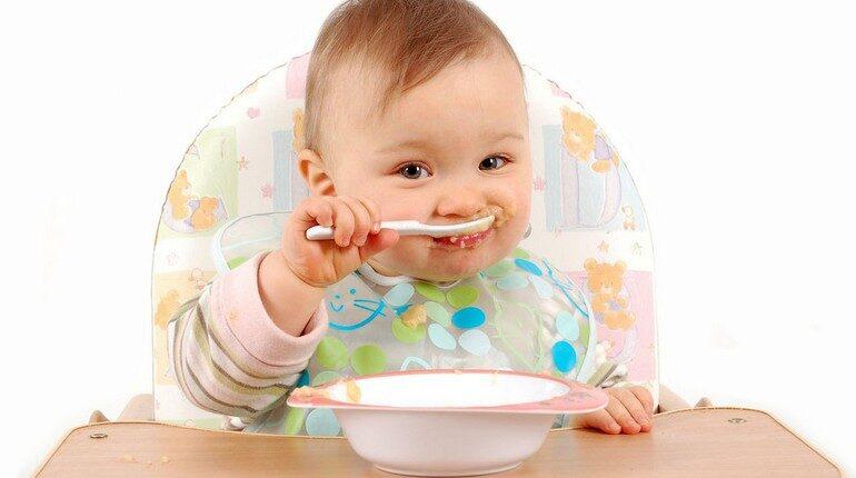 малыш сам кушает с ложечки, ребенок сидит в стульчике для кормления и кушает ложкой, младенец кушает