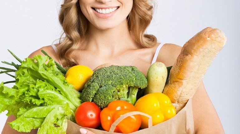 девушка держит в руке пакет с овоща и хлебом