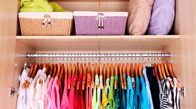 идеальный порядок в шкафу, вещи развешены по цветам, все сложено аккуратно в шкафу