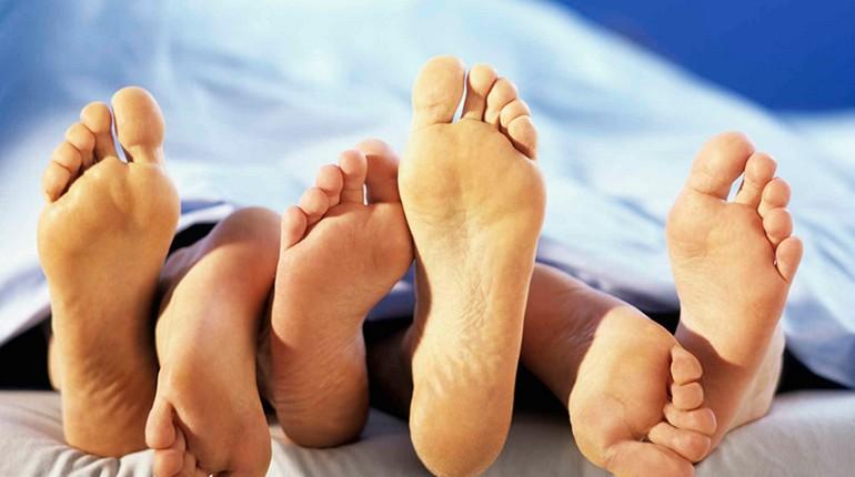 трое в постели, три пары ног торчат из-под одеяла