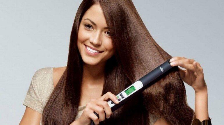 девушка выравнивает волосы щипцами