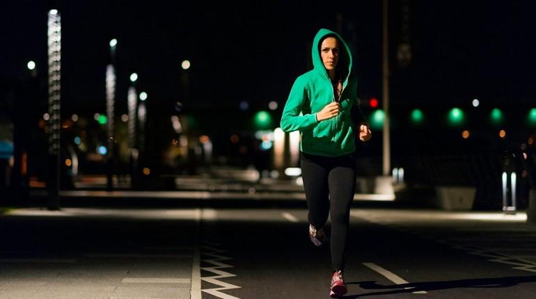 вечерняя пробежка, девушка в капюшоне бежит по вечернему городу