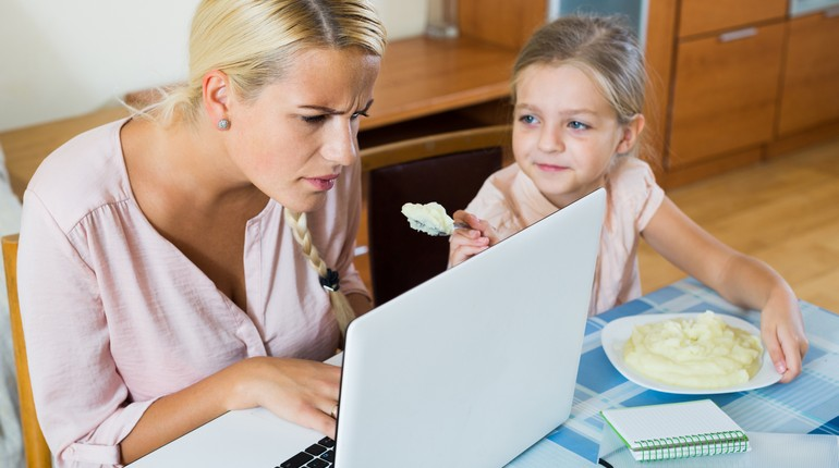 девушка сосредоточенно смотрит в экран монитора и дочка кормит ее обедом, увлеченная работа в домашней обстановке