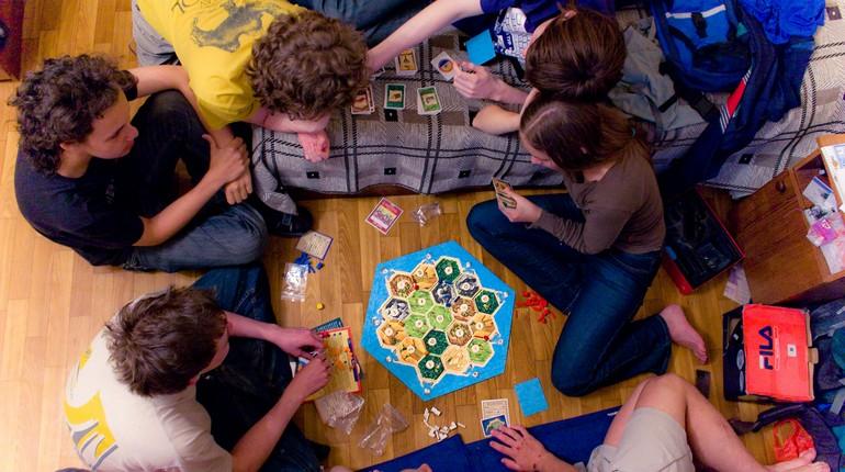 молодые люди играют в настольные игры, компания друзей играют в игру