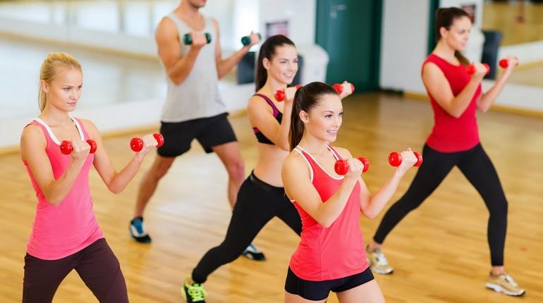 девушки занимаются с гантелями, занятие по кроссфиту в спортклубе