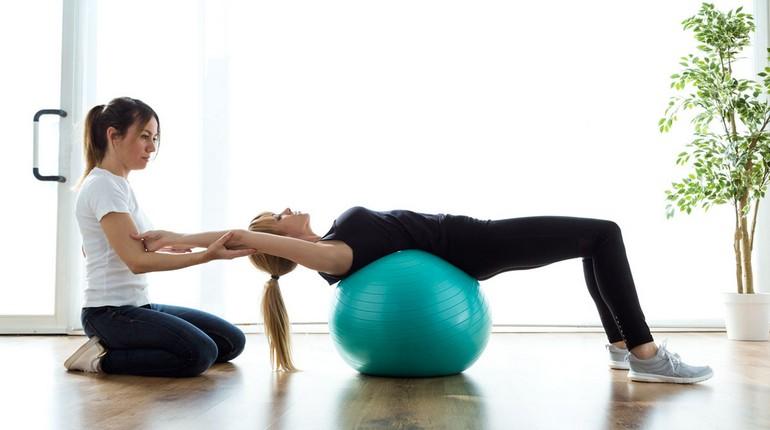 девушка делает упражнения кегеля с инструктором, гимнастика на фитболе