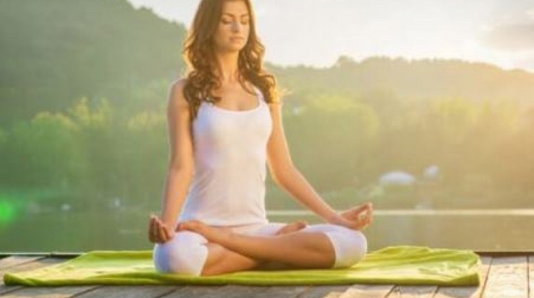 девушка сидит в позе лотоса и медитирует, медитация на свежем воздухе