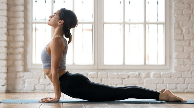 упражнение кобра, девушка делает упражнения для спины