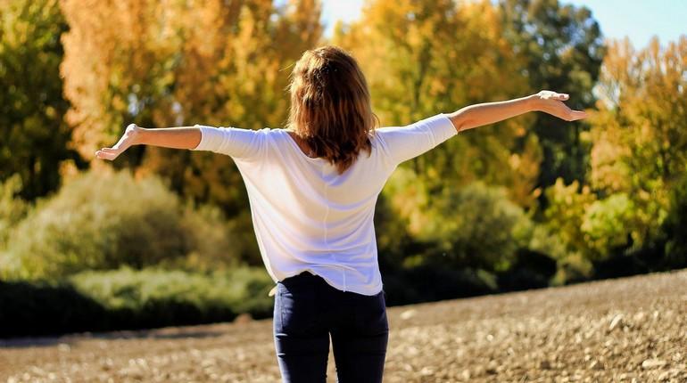 девушка на улице делает дыхательную гимнастику, занятия на свежем воздухе