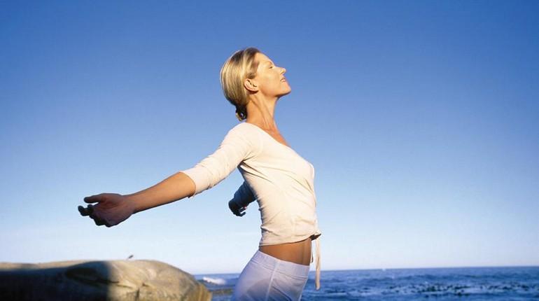 дыхательные упражнения на берегу моря, девушка занимается утренней гимнастикой на пляже