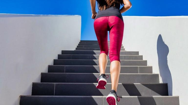 пробежка по лестнице, девушка в спортивной одежде бежит вверх по лестнице