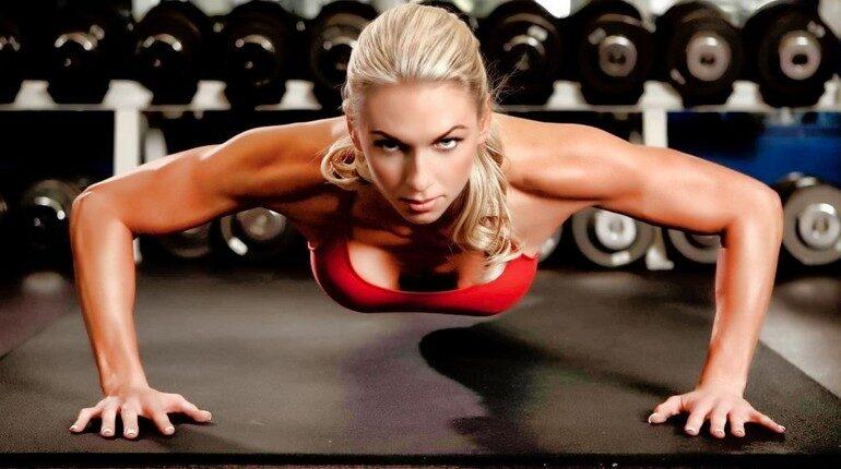 девушка делает отжимания в тренажерном зале, упражнения на грудные мышцы