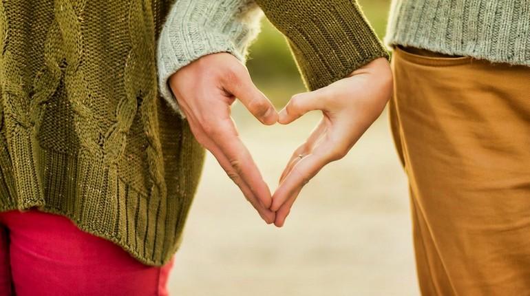 парень с девушкой держатся за руки, парочка сложила руки сердечком