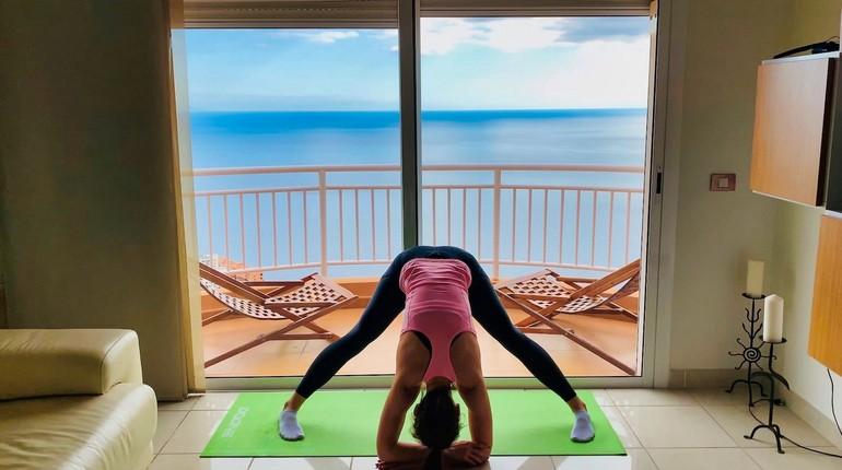 девушка тренируется дома, тренировки с видом на море, девушка делает наклоны вперед
