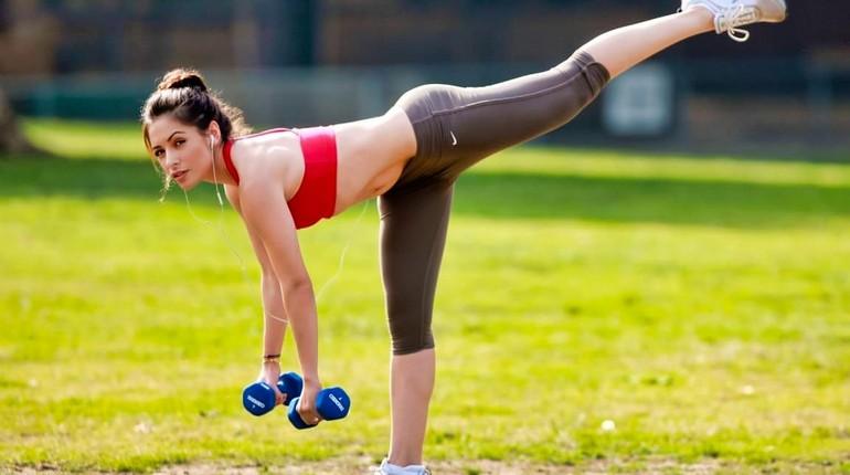 тренировка с гантелями на свежем воздухе, девушка занимается на улице летом