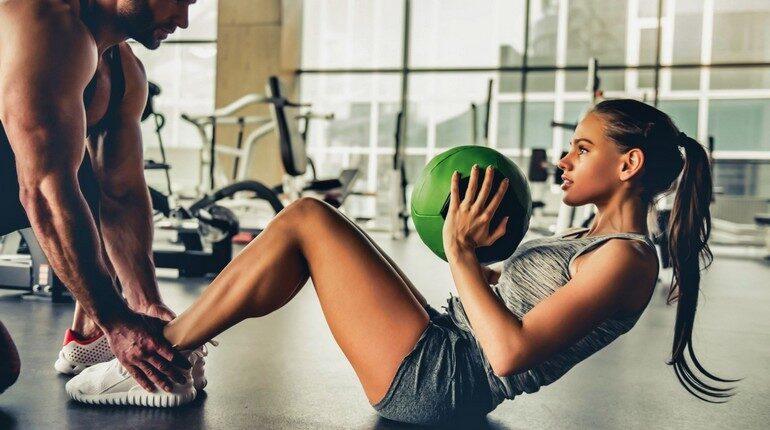 девушка занимается с тренером в тренажерном зале, тренировка с мячом , упражнения для укрепления пресса