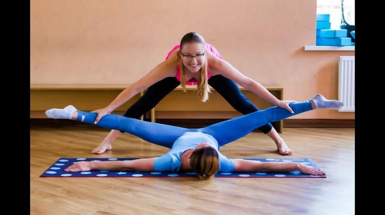 выполняем упражнения на растяжку с помощью подруги, девушка хочет сесть на шпагат, растяжка перед шпагатом