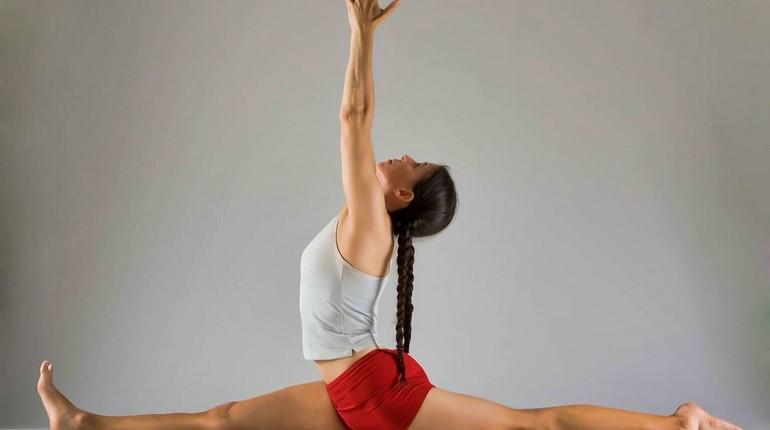 девушка сидит на шпагате, занятие гимнастикой