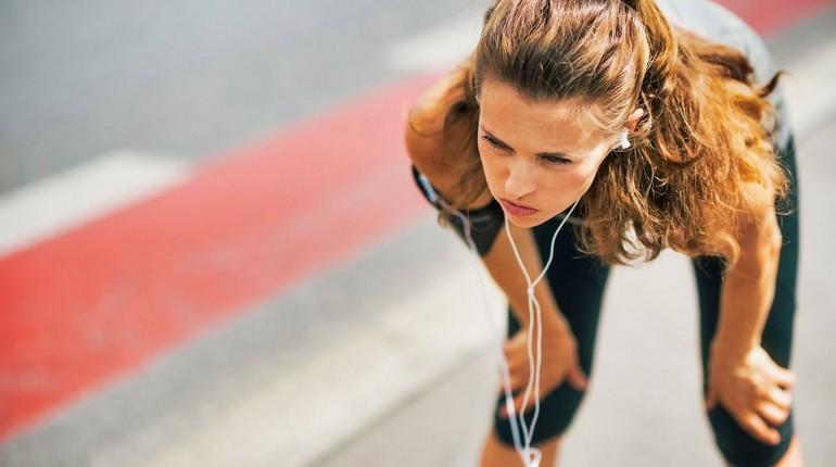 девушка устала на пробежке, проблемы с дыханием на тренировке