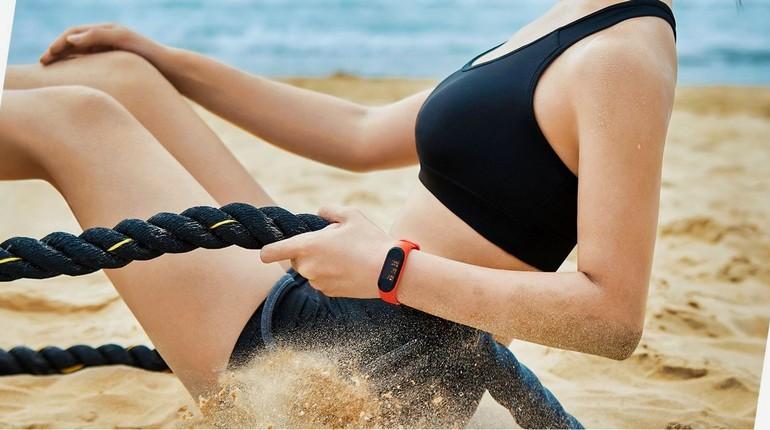у девушки на руке фитнес-браслет, тренировка с фитнес-трекером