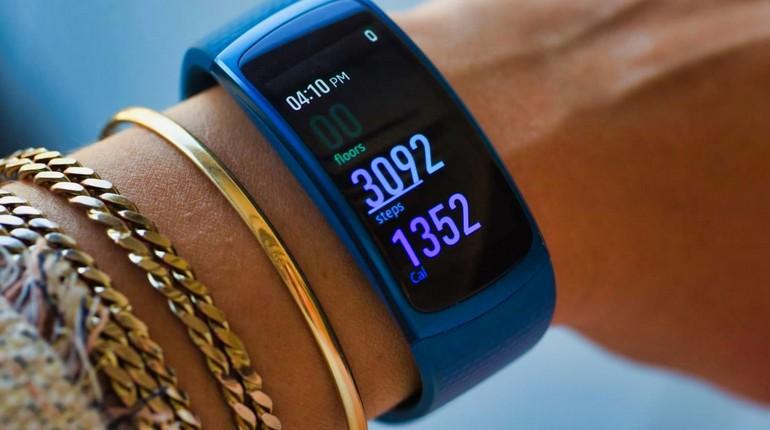 современные приспособления для максимальных удобств при занятии спортом, фитнес браслет на запястье у девушки