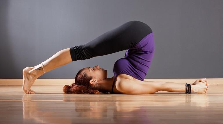 девушка делает ассаны, упражнение йоги, тренировка в зале