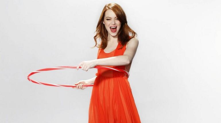 девушка в ярком оранжевом платье крутит хула хуп, обруч для похудения, девушка крутит обруч на талии