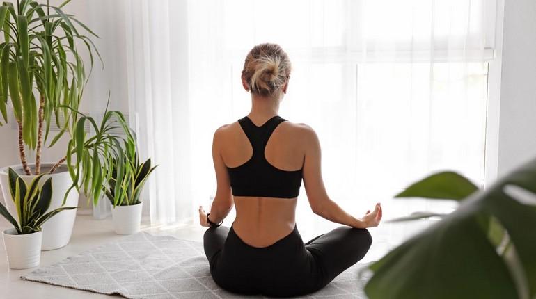 девушка медитирует, медитация в позе лотоса, девушка занимается йогой