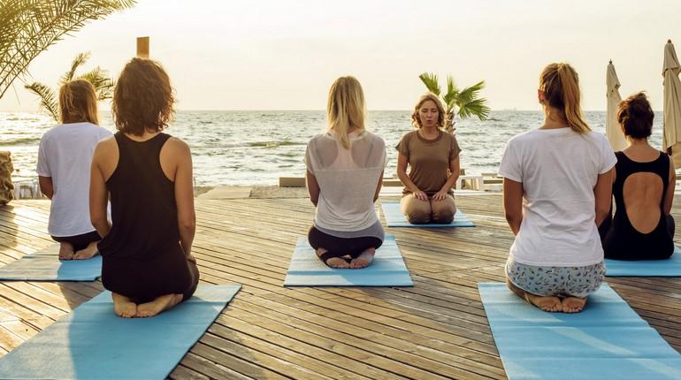 занятия йогой в группе на берегу моря, медитация под шум прибоя, девушки на занятиях йогой