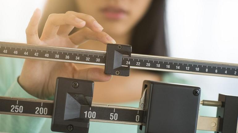 девушка проверяет свой вес, взвешивание после праздников